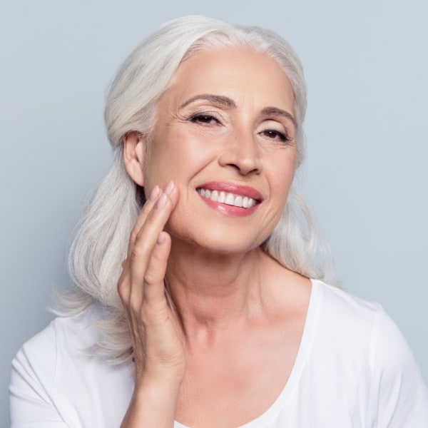 Close up of older woman smiling touching her face