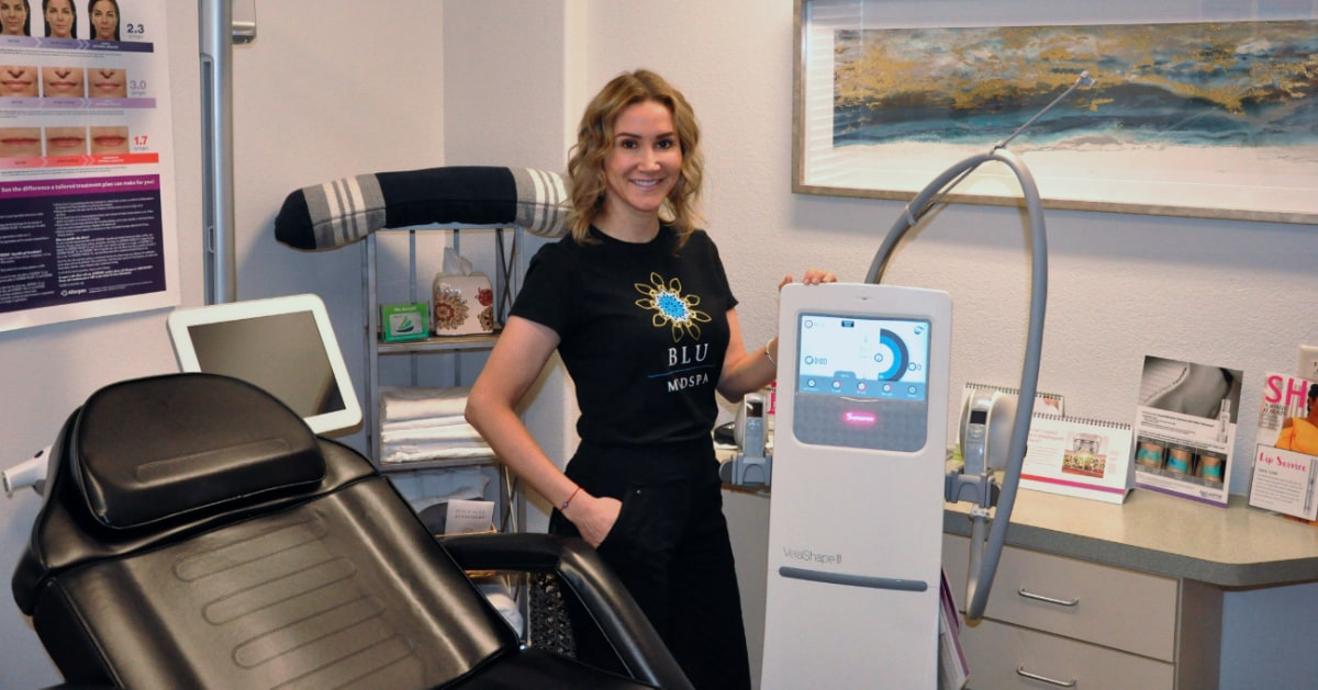 BLU Medspa staff member posing with VelaShape III equipment in treatment room
