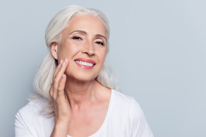 beautiful older woman with gray hair and smooth skin touching face