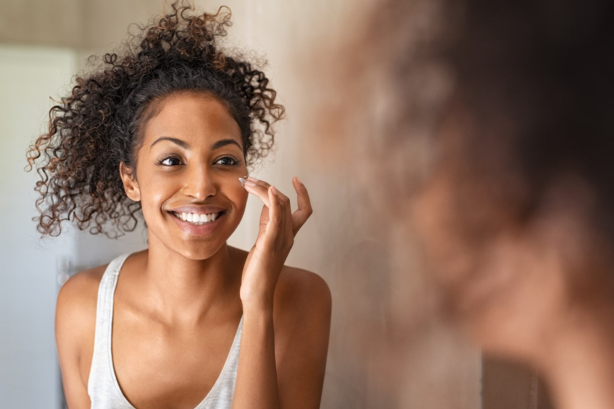 young woman looking in mirror applying cream to her face