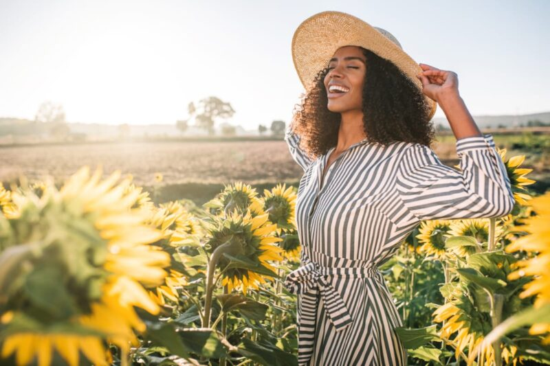 Smiling woman with sun hat and striped dress in field on sunflowers