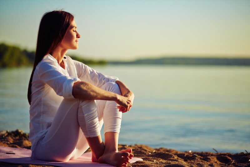 Woman sitting on beach with eyes closed meditating